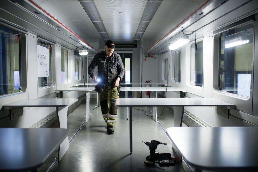 REDAKSJONSLOKALE: Mekaniker Jacob Øvergaard fra Mantena monterer bord i en av B5-vognene som skal fungere både som sittevogn og redaksjonslokale.