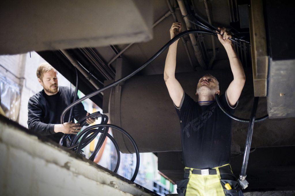KABLER: Mye arbeid har skjedd under vognene, blant annet for å sikre kraftigere strømtilførsel. Her er Paul Schiager og Ståle Stenhaug fra Mantena i arbeid under F7-en, det vil si regi-vogna.