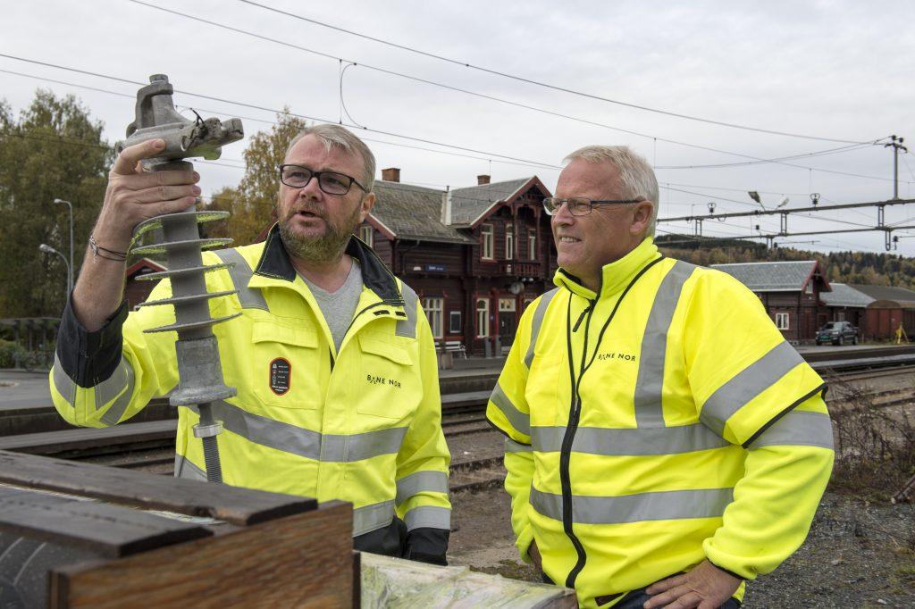 RYKKER UT RASKT: Reidar Woldengen (t.v.) og Harald Tanum, faggruppeledere for strømforsyning og linjen, sørger for at akutt feilretting gjennomføres raskt på Gjøvikbanen. For tida erstatter de kjeramiske isolatorer med kompositt.